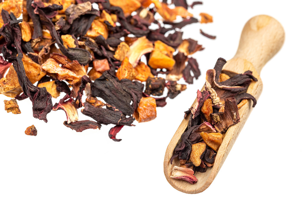 Dried hibiscus petals with dried fruits on a white background with a wooden scoop