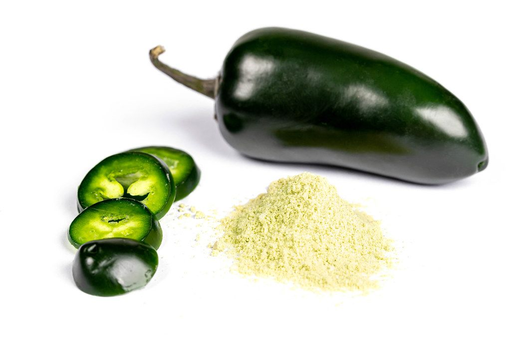 Dried powder and fresh jalapeno pepper on white