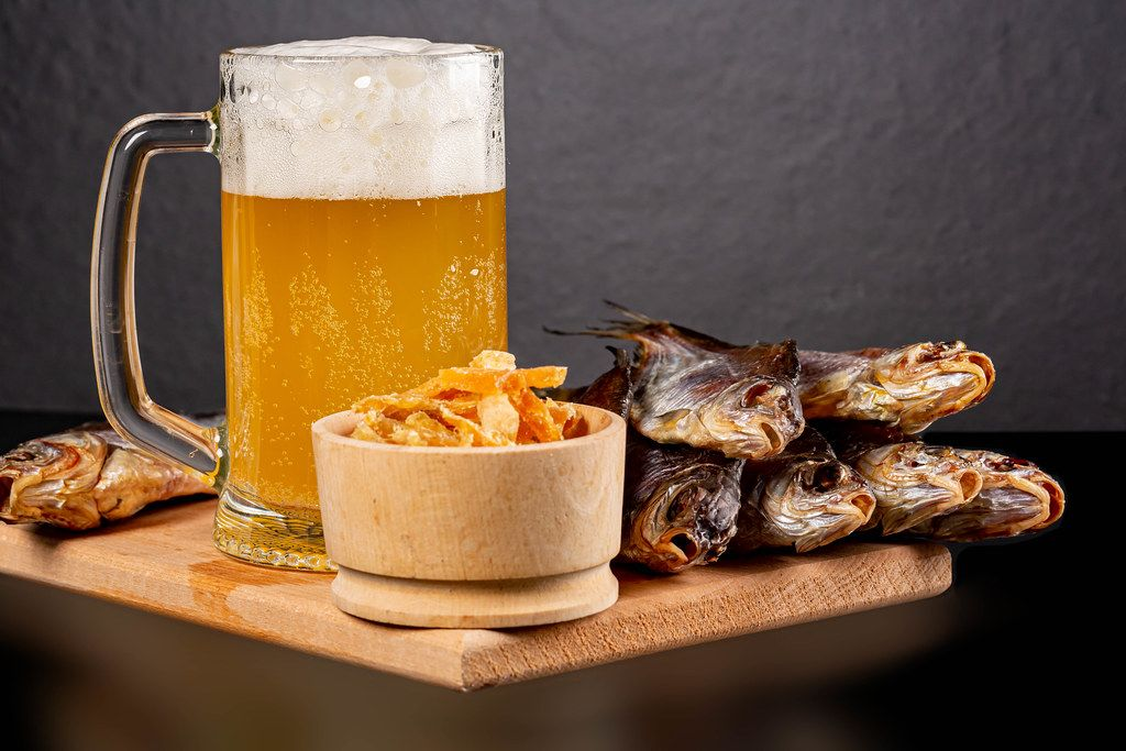 Dried roach fish and tuna with a glass of unfiltered beer