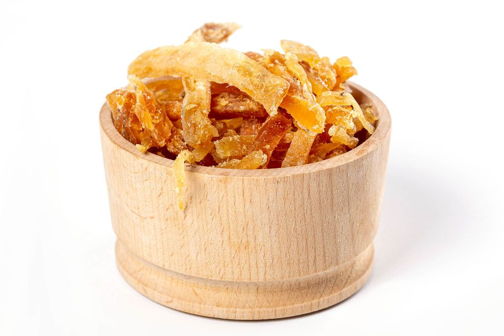 Dried salted tuna meat strips in wooden bowl on white