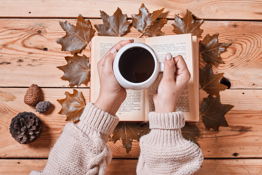 Drinking hot coffee in a cold autumn morning and reading a book
