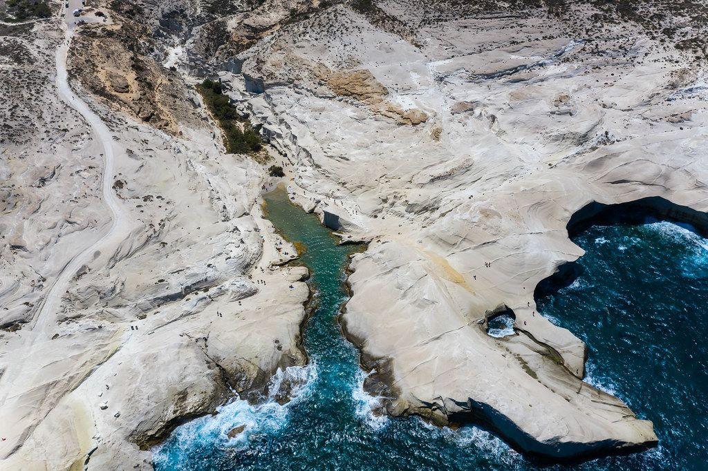 Drohnenaufnahme an der griechischen Küste auf Milos mit weißen Klippen, kleiner Bucht, rauem Meer