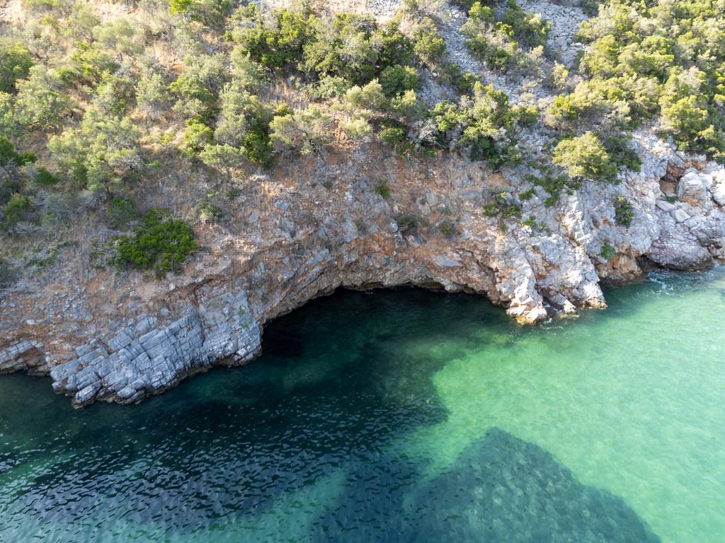 Drohnenaufnahme der Felsküste mit smaragdgrünem Wasser beim Strand Limnonari, Skopelos