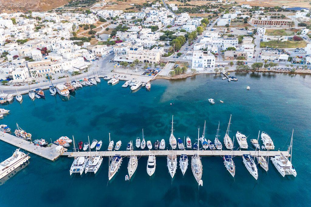 Drohnenaufnahme der Hafenstadt Adamantas. Pier mit Segelbooten und Jachten und das blaue Meer