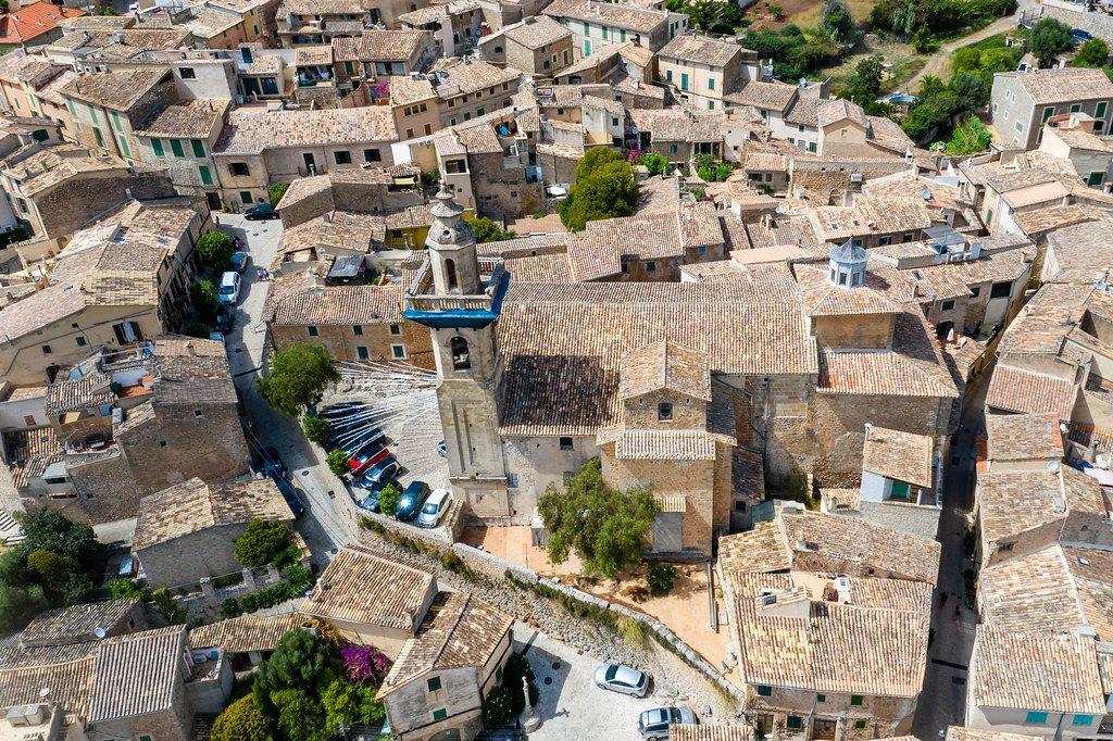 Drohnenaufnahme: Die Kirche St. Bartholomäus und die gut erhaltene Altstadt von Valldemossa, Mallorca