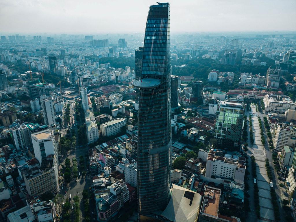 Drohnenaufnahme vom Bitexco Financial Tower mit Helikopter Landefläche neben der leeren Nguyen Hue Fußgängerzone und dem Ben Thanh Markt im Hintergrund in Ho Chi Minh Stadt, Vietnam
