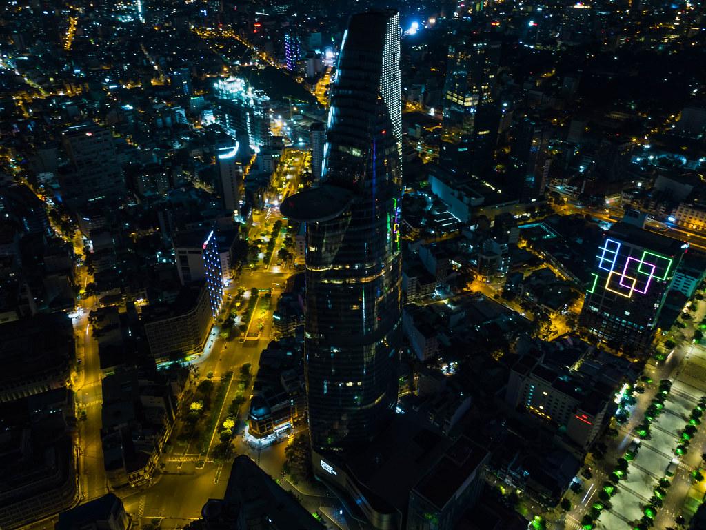 Drohnenaufnahme vom Bitexco Financial Tower mit Helikopter Landefläche neben der Nguyen Hue Fußgängerzone bei Nacht in Ho Chi Minh Stadt, Vietnam