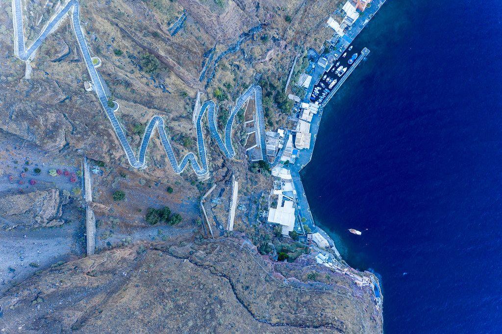 Drohnenaufnahme vom Hafen Firás mit dem steilen Fußweg, der zur Stadt führt