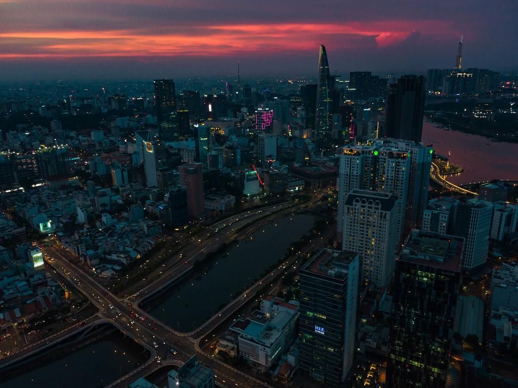 Drohnenaufnahme vom Stadtzentrum mit Bitexco Financial Tower, anderen Hochhäusern und Saigon River mit Landmark 81 im Hintergrund bei Nacht in Ho Chi Minh Stadt, Vietnam