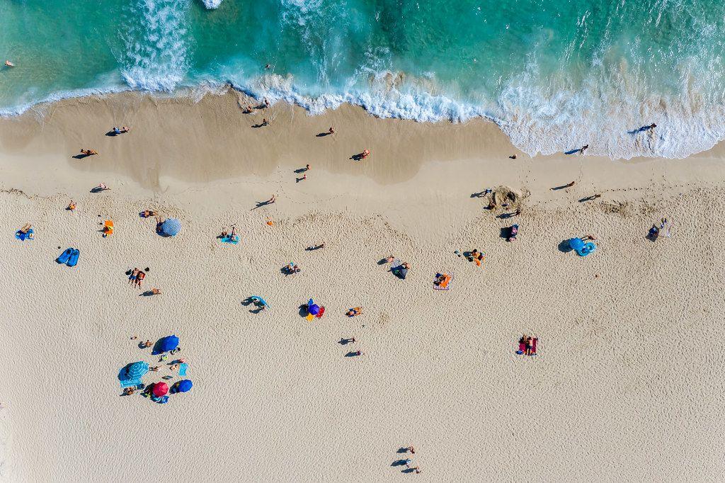 Drohnenaufnahme vom Strand Cala Mesquida auf Mallorca mit Wellen, Sand und Touristen