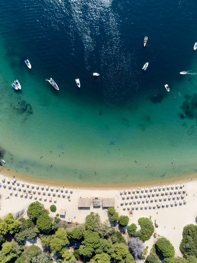 Drohnenaufnahme vom Strand mit türkisblauem Wasser auf der Insel Tsoungria bei Skiathos