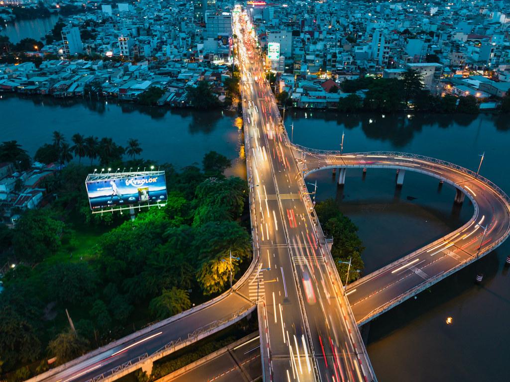 Drohnenaufnahme von einem kleinen Stadtpark, Gebäuden und Verkehr auf einer Brücke über dem Saigon Fluss mit Langzeitbelichtung in Ho Chi Minh Stadt, Vietnam