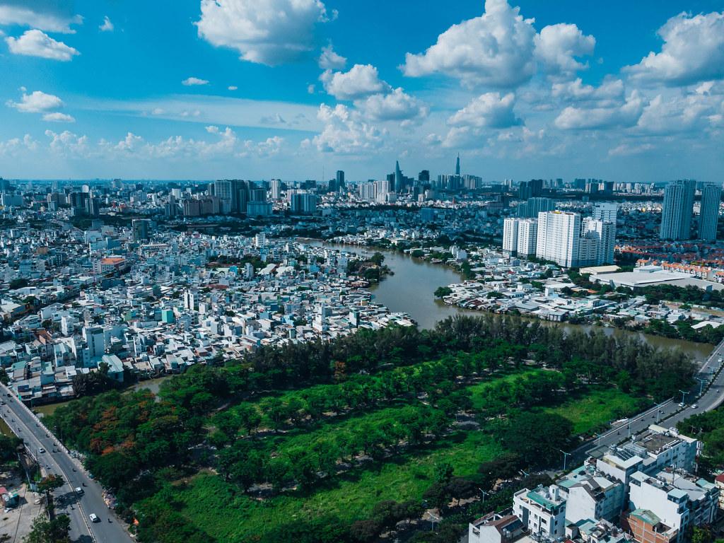 Drohnenaufnahme von einem öffentlichen Park neben dem Saigon Fluss in Distrikt 8 und der Skyline mit Bitexco Financial Tower und Landmark 81 in Ho Chi Minh Stadt, Vietnam