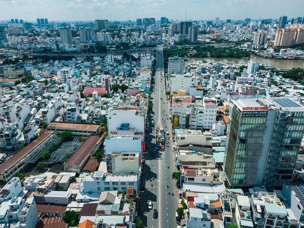 Drohnenaufnahme von Häusern, Bürogebäude, Kirche und einer Schule entlang einer Straße in Distrikt 8 welche zu einer Brücke über den Saigon Fluss führt in Ho Chi Minh City, Vietnam