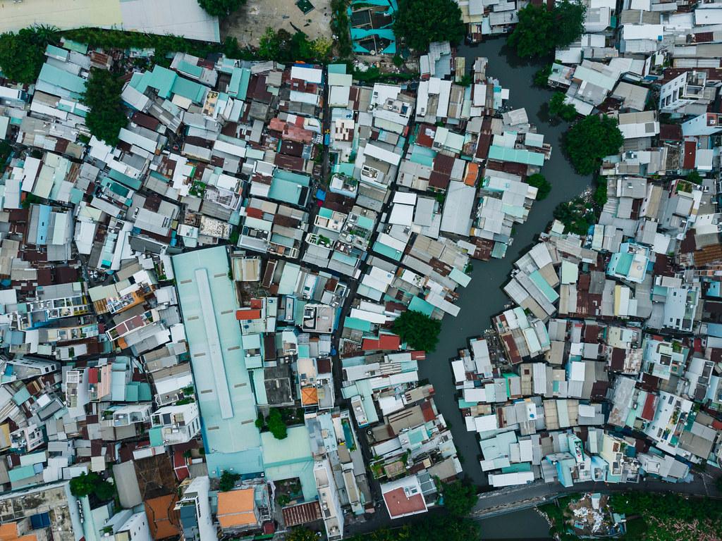 Drohnenaufnahme von Häusern in einem Wohngebiet neben einem kleinen Fluss in der Vogelperspektive in Ho Chi Minh Stadt, Vietnam