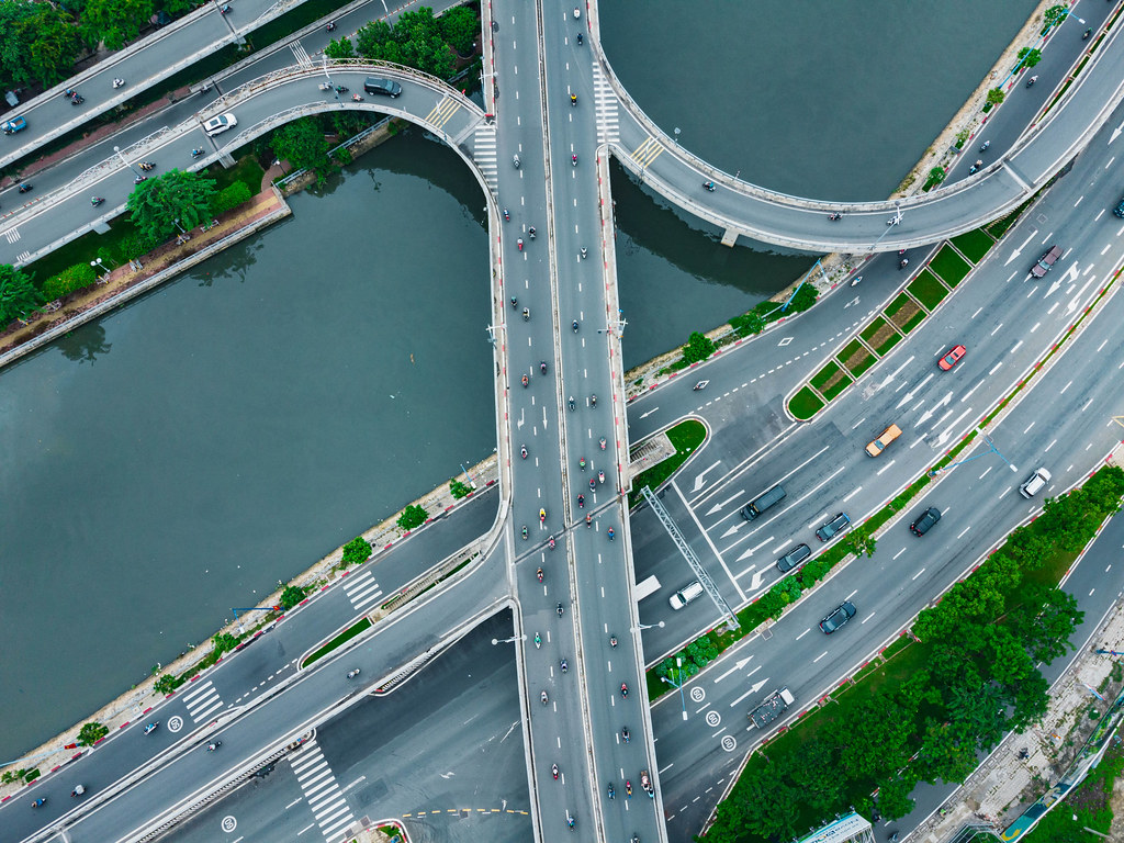 Drohnenaufnahme von Motorrollern und Autos auf einer Brücke über dem Saigon Fluss und einer Autobahn in Ho Chi Minh Stadt, Vietnam