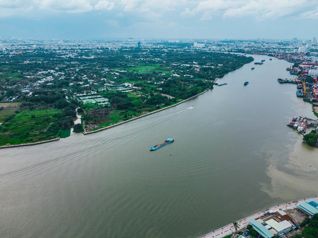 Drohnenaufnahme von Transport-Schiffen am Umschlag Hafen und auf dem Saigon Fluss in Ho Chi Minh Stadt