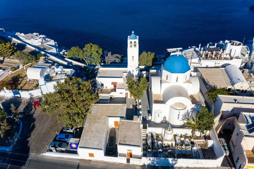 Drohnenaufnahme. Weiße Kirche und Glockenturm mit blauen Kuppeln und Friedhof auf Santorin