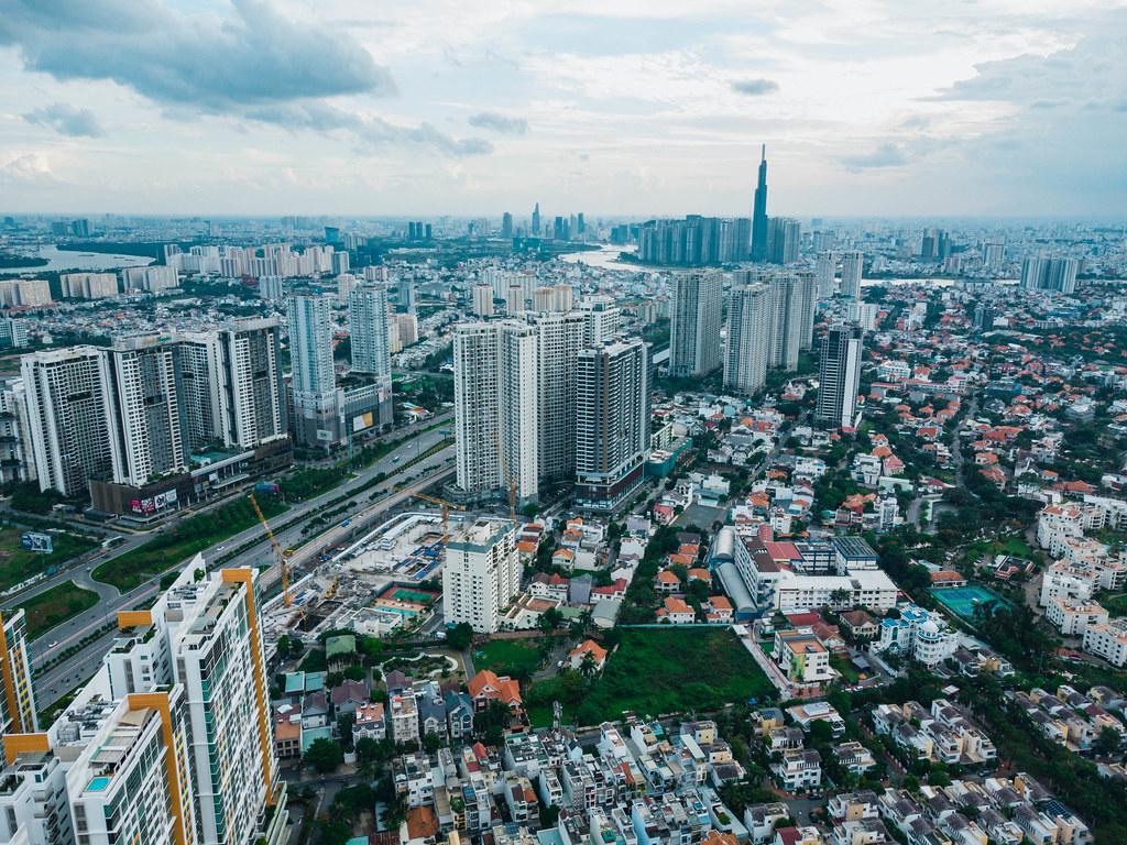 Drohnenbild der Ho Chi Minh Stadt Skyline mit vielen Apartmentgebäuden, Landmark 81, Saigon River und Bitexco Financial Tower in Vietnam