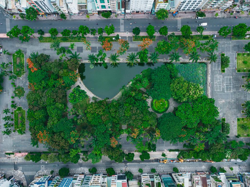 Drohnenfoto vom geschlossenen 23/9 Park mit vielen Bäumen und einem kleinen See im Stadtzentrum von Ho Chi Minh City, Vietnam