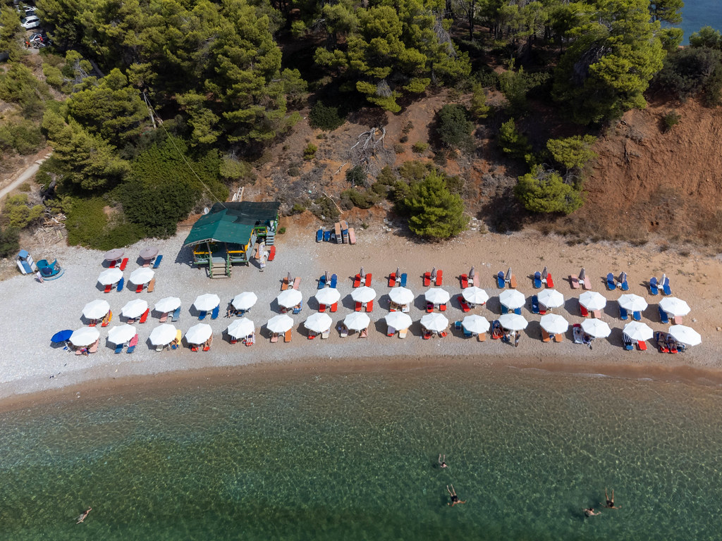 Drone image of Kokkinokastro beach with rows of white parasols and sunbeds on the Greek island of Alonnisos
