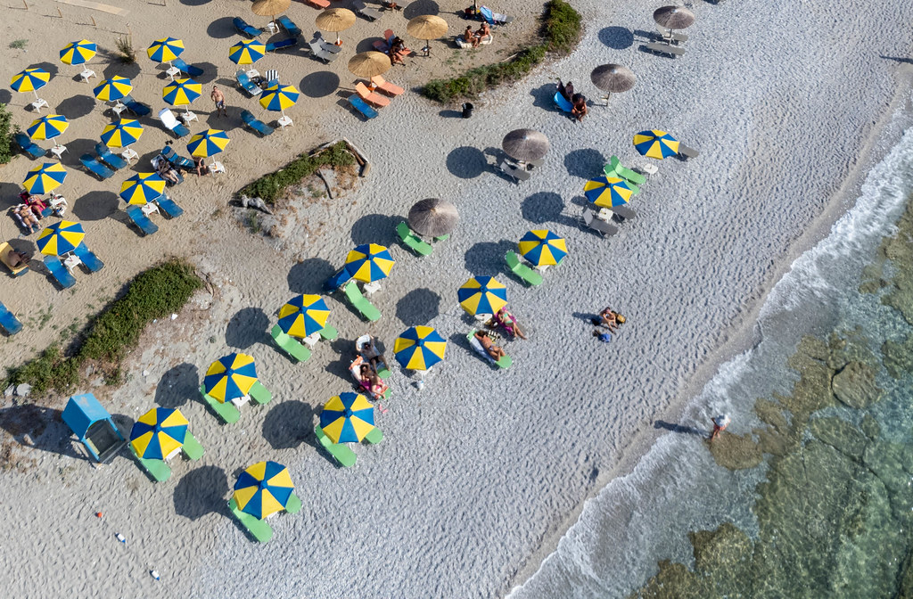 Drone image of Milia Beach on Skopelos with rows of blue and yellow parasols on the sandy beach