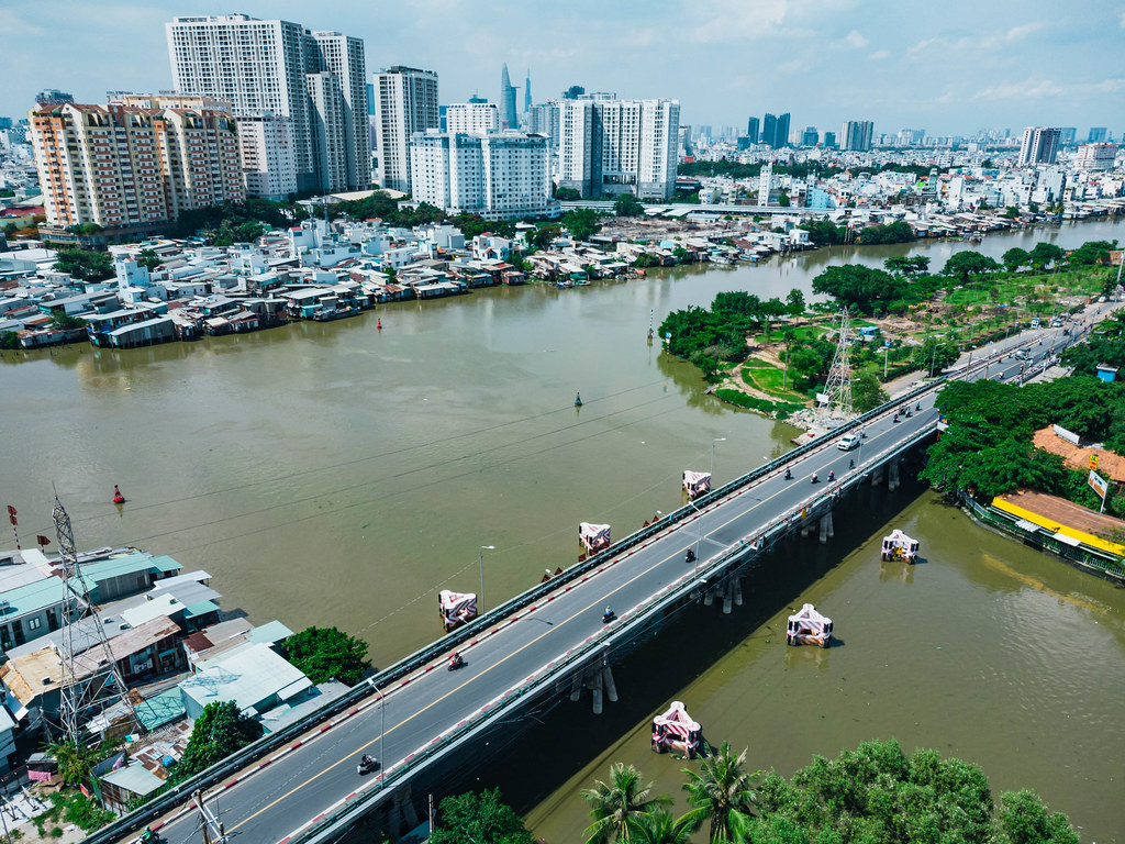 Drone Photo of a Bridge and Power Lines over Saigon River with Apartment Buildings, Bitexco Financial Tower and Landmark 81 in the Background in Ho Chi Minh City, Vietnam