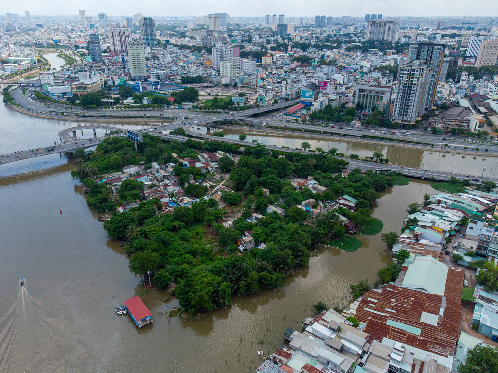 Drone Photo of a Bridge connecting a small Island with other Districts, Boats on Saigon River and many Buildings in Ho Chi Minh City, Vietnam