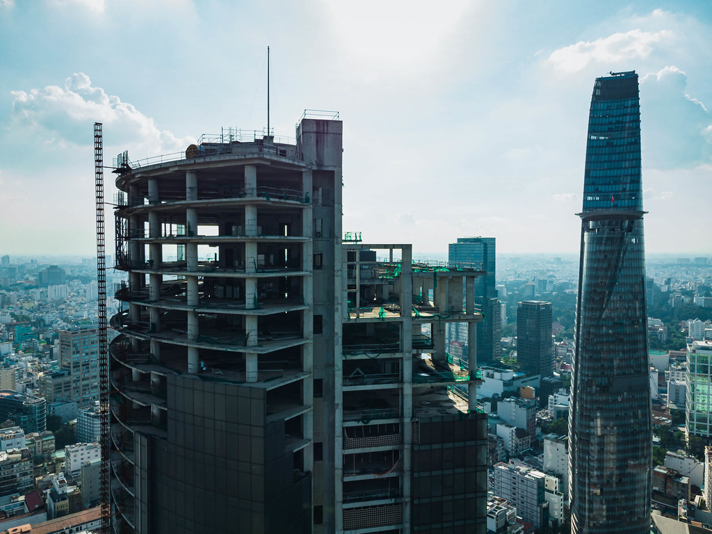 Drone Photo of abandoned Saigon One Tower Construction with Bitexco Financial Tower in the Background in Ho Chi Minh City, Vietnam