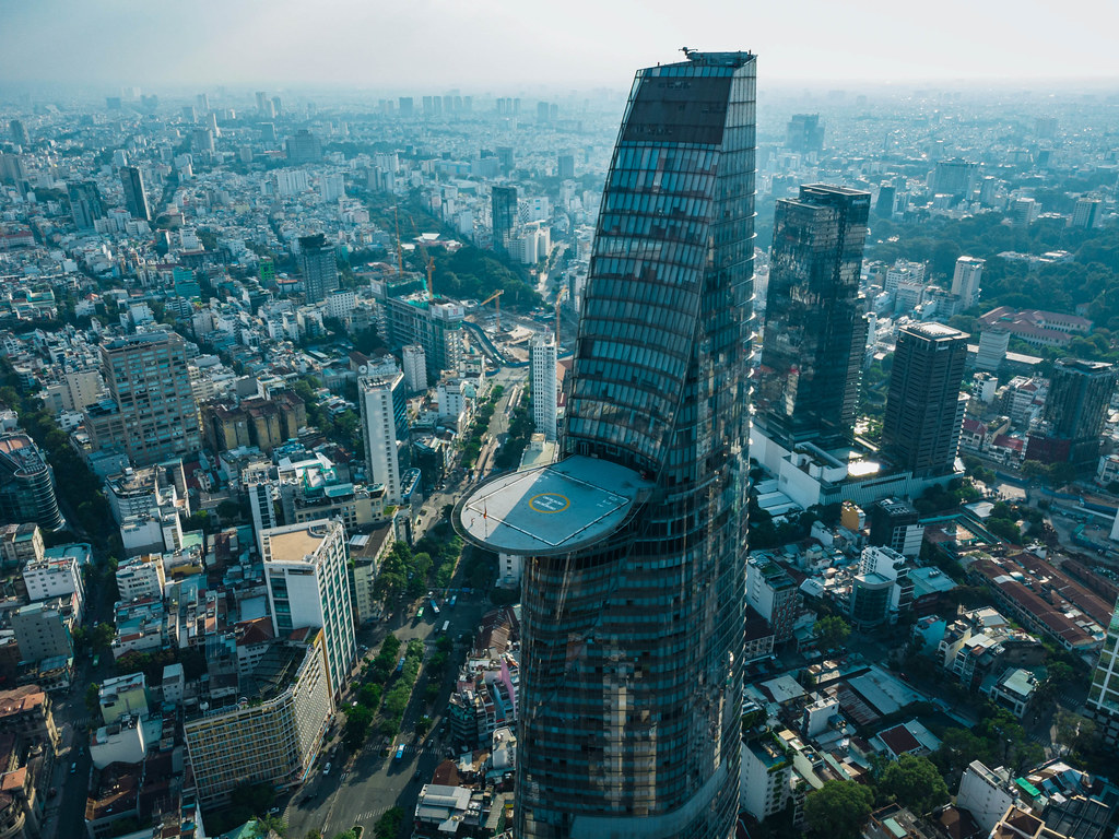 Drone Photo of Bitexco Financial Tower with cantilevered Helipad on the 55th Floor in the Center of District 1 with Public Parks, Constructions and Buildings in the Background in Ho Chi Minh City, Vietnam