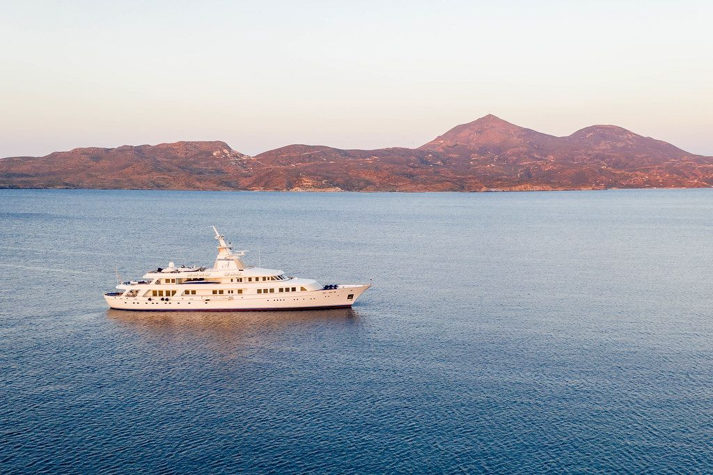 Drone photo of Blohm + Voss superyacht Astarte II at sunset at sea in Adamantas, Milos, Cyclades