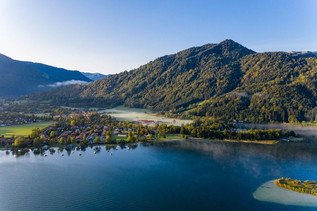 Drone photo of Lake Tegernsee with crystal clear blue water and the surrounding alpine mountains