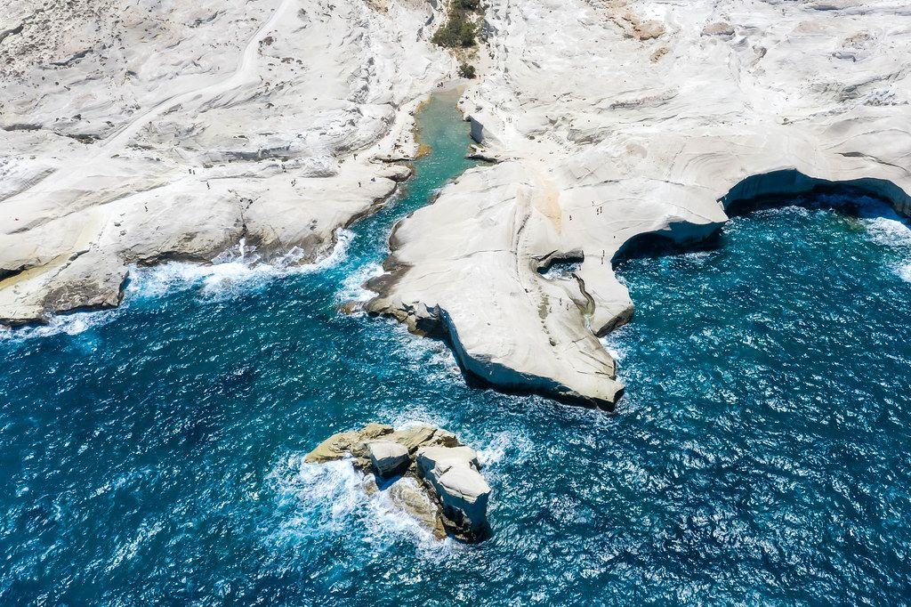 Drone photo of Sarakiniko on the Greek island of Milos with white cliffs, small bays and rough sea
