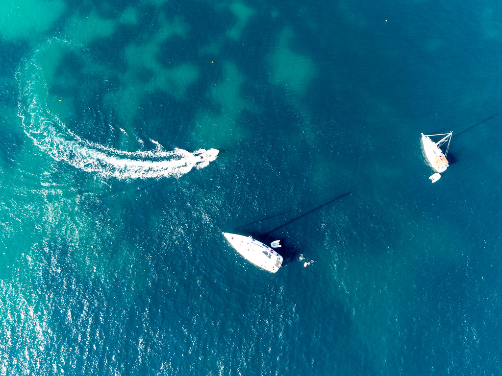 Drone photo of three boats and some people swimming in the crystal clear waters of Skopelos, Greece