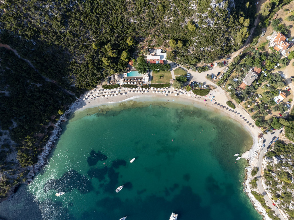 Drone photography in Greece: the bay of Limnonari with beach, swimming pool, pine forest and boats