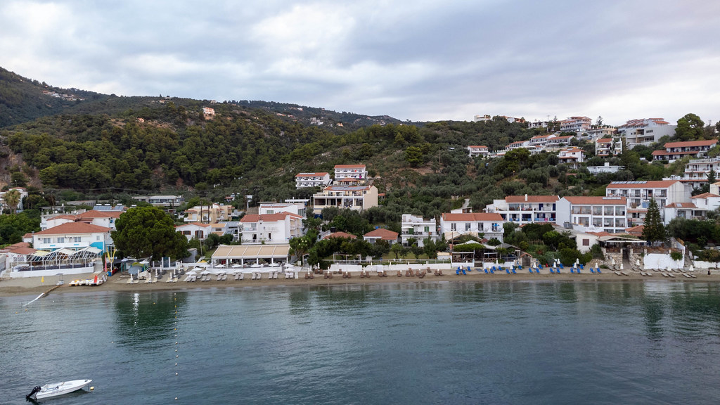 Drone shot of the hilly coast of Greek island Skiathos with houses directly on the beach: Paralia Megali Ammos