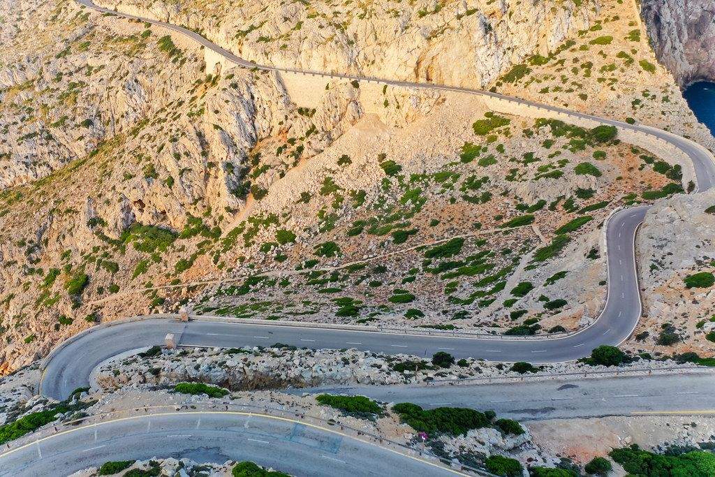 Drone shot of the snake road climbing up to the top of the rocky Cap de Formentor headland in Majorca