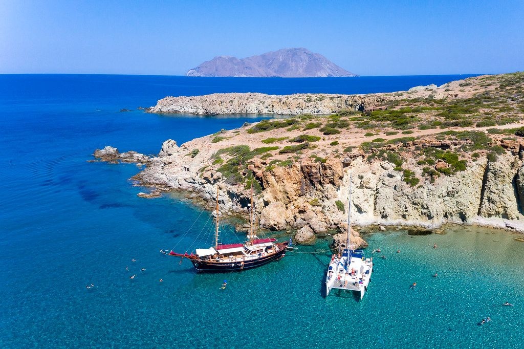 Drone shot of two boats and the sea on a catamaran daily excursion on the island of Milos, Greece