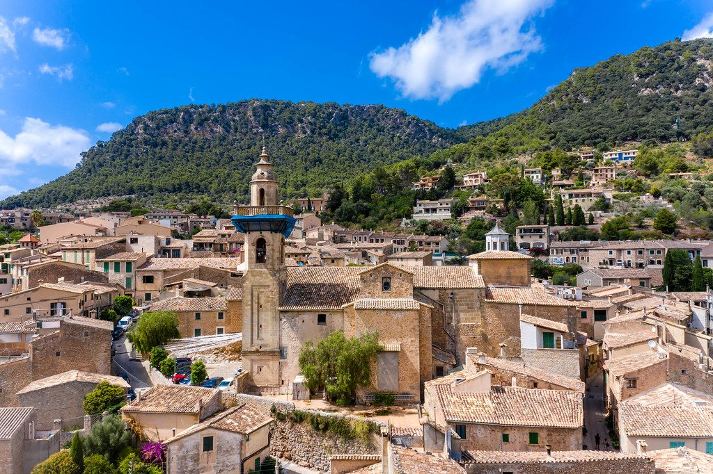 Drone shot: St. Bartholomew church and the well-preserved old town of Valldemossa, Mallorca