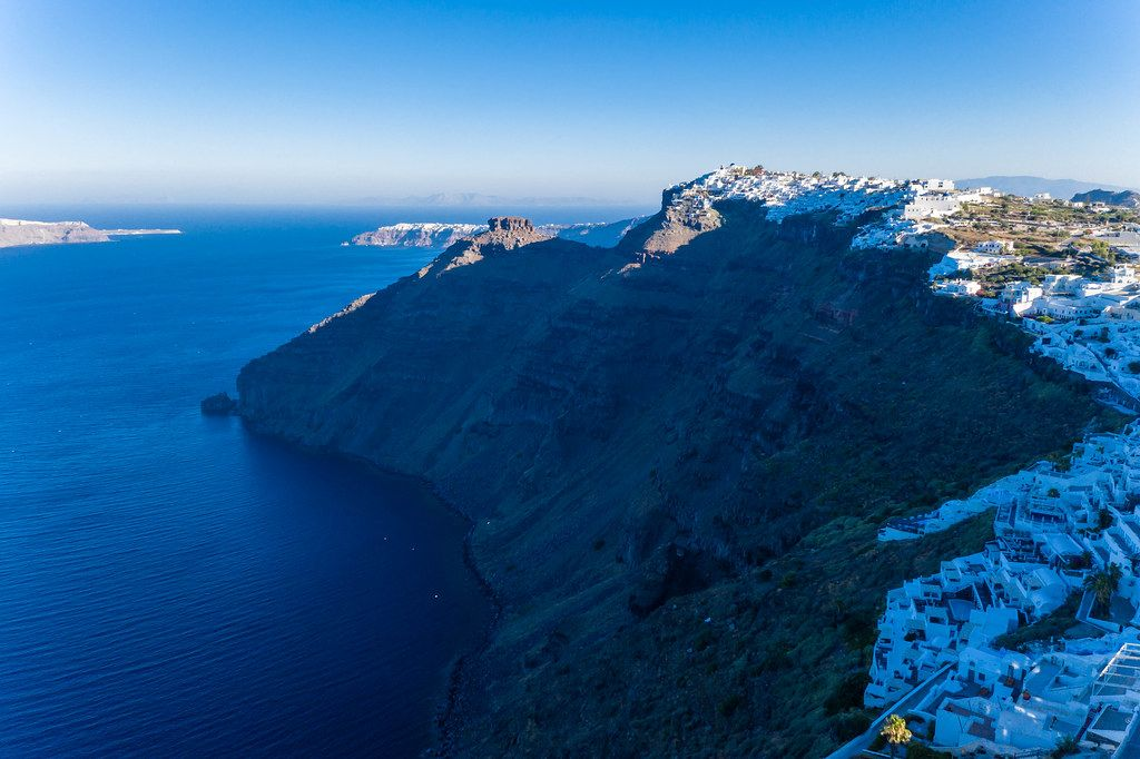 Drone shot: the volcanic cliffs of Santorini, the sea and the capital of the island, Firá in blue light