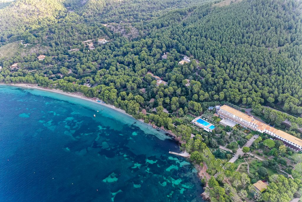 Drone shot: the world famous Formentor Royal Hideway Hotel surrounded by pine trees on Majorca