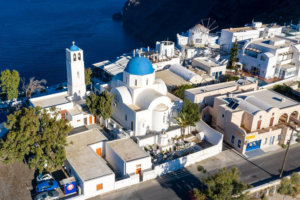 Drone shot. White church and bell tower with typical blue domes, cemetery and windmill in Santorini