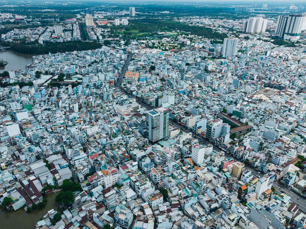 Dronenaufnahme von Distrikt 8 mit vielen Häusern, Wohngegenden und Straßen mit Nha Be Stadtbezirk im Hintergrund in Ho Chi Minh Stadt, Vietnam