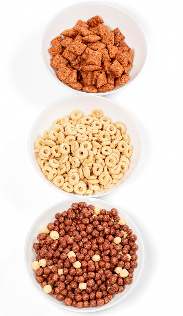 Dry breakfast cereals in bowls on white