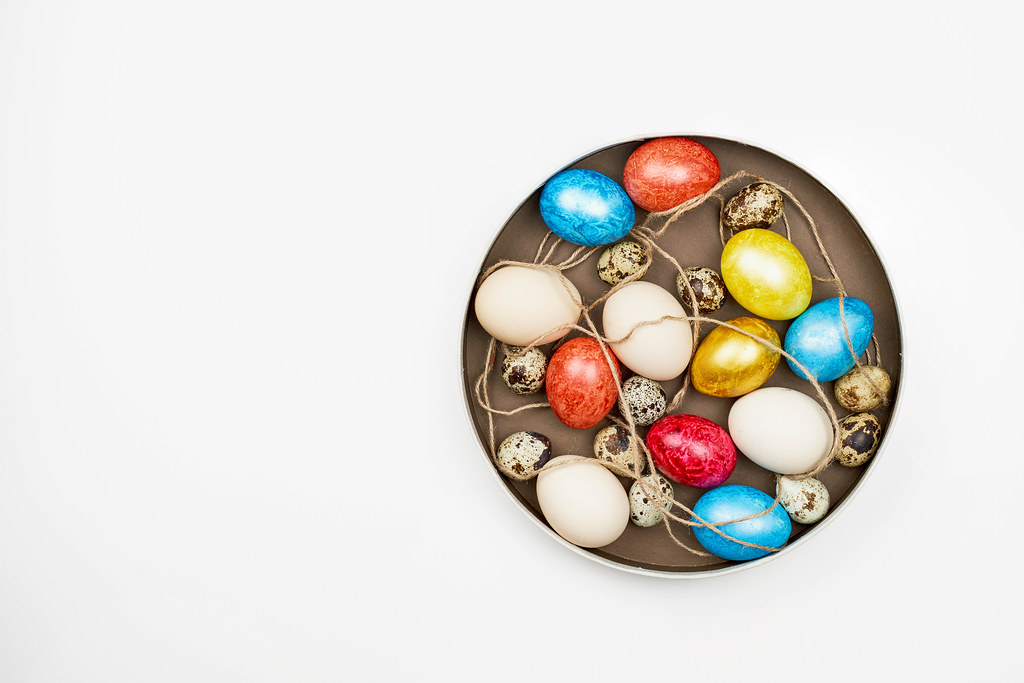Dyed and non-dyed easter eggs and quail eggs on a plate, top view on white background with copy space