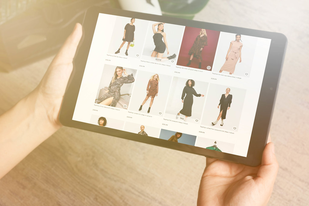 E-commerce and online shopping concept - woman choosing clothing