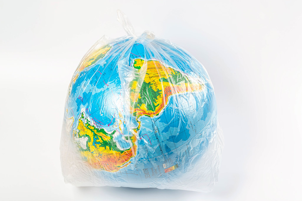 Earth in polyethylene plastic disposable package on white background. Concept pollution of environment with polyethylene plastic waste, ecological problems