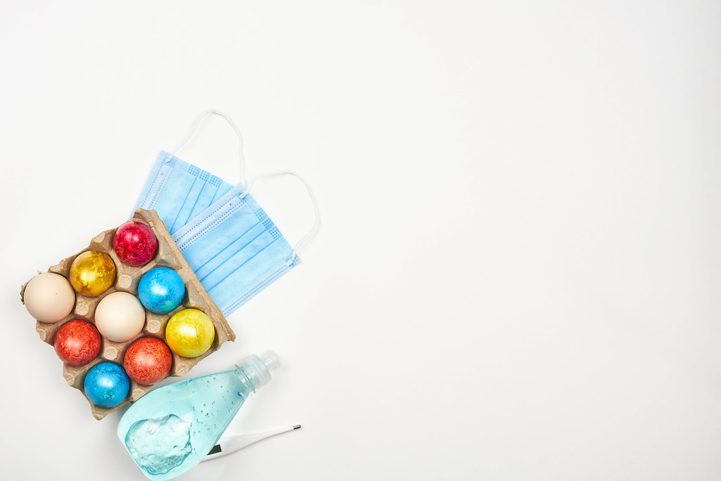 Easter and Covid-19: dyed eggs in a carton, hand sanitizer, thermometer, face masks and copy space