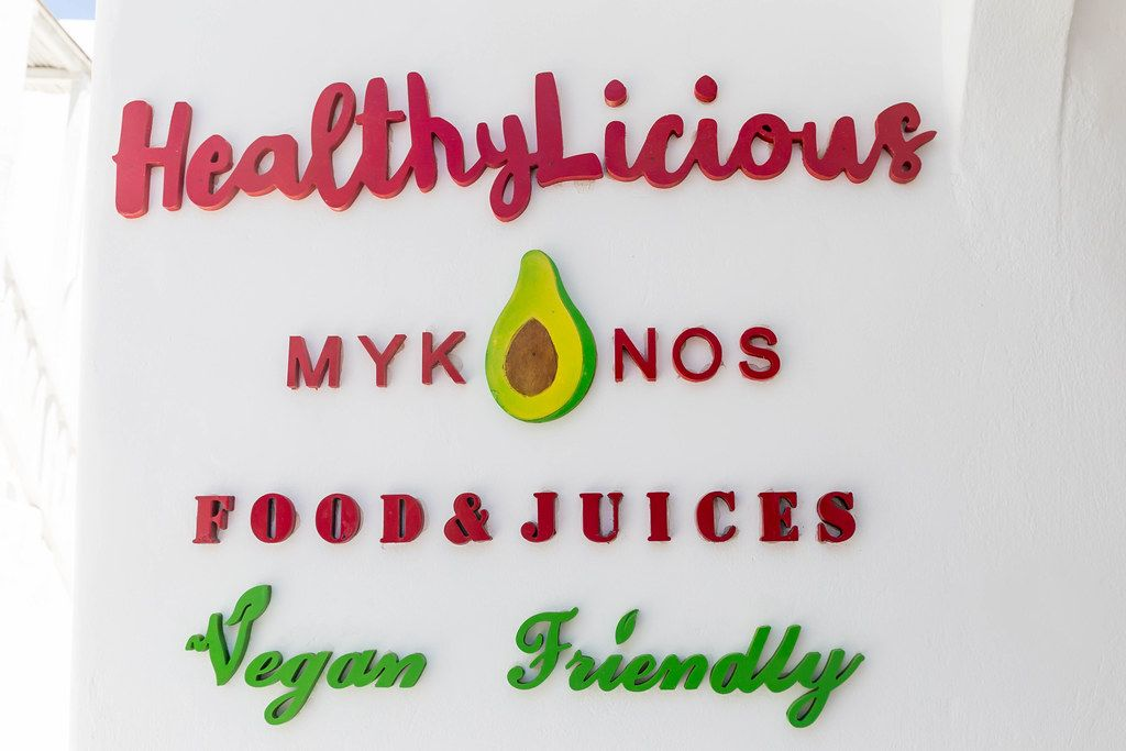 Eating vegan in Mykonos: HealthyLicious Food & Juices restaurant. Sign on white wall
