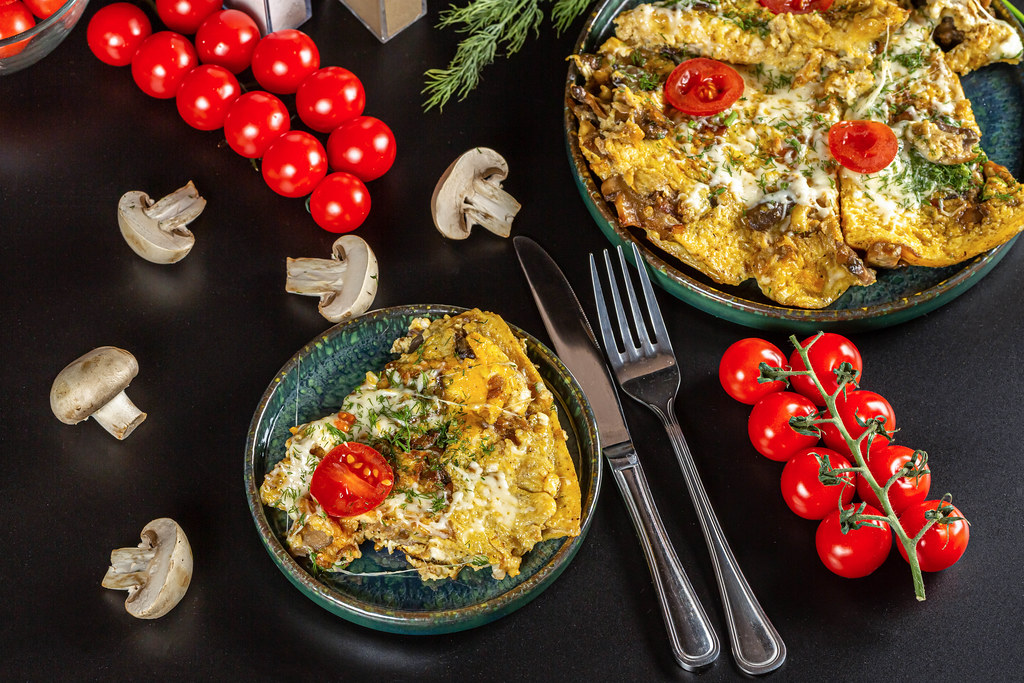Egg omelet with mushrooms, cheese, tomatoes and herbs on a dark background